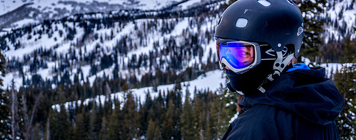 A skier in a ski mask and helmet standing in front of snow-covered pines as a backdrop